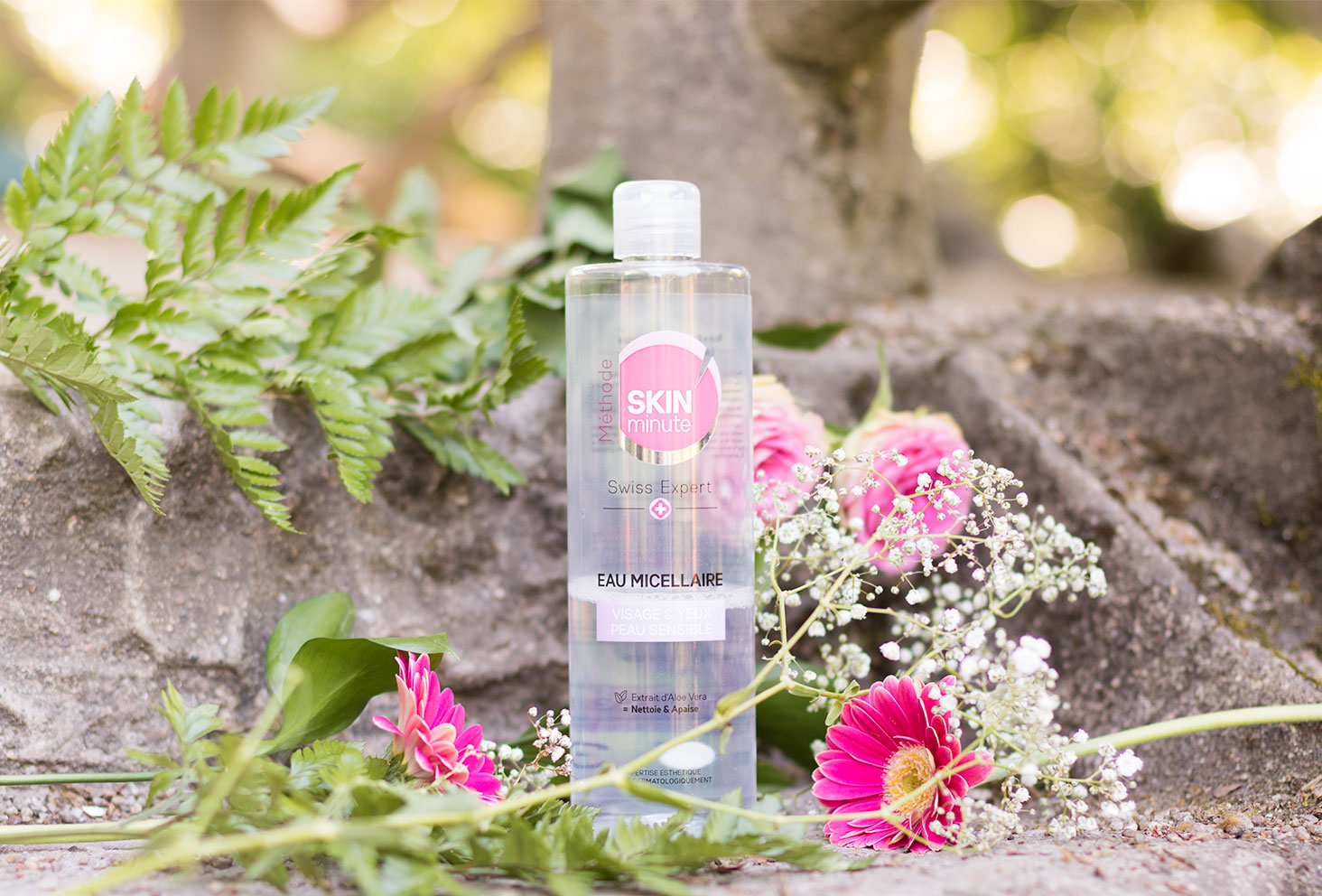 L'eau micellaire de Body Minute entre les fleurs roses et blanches sur un pierre