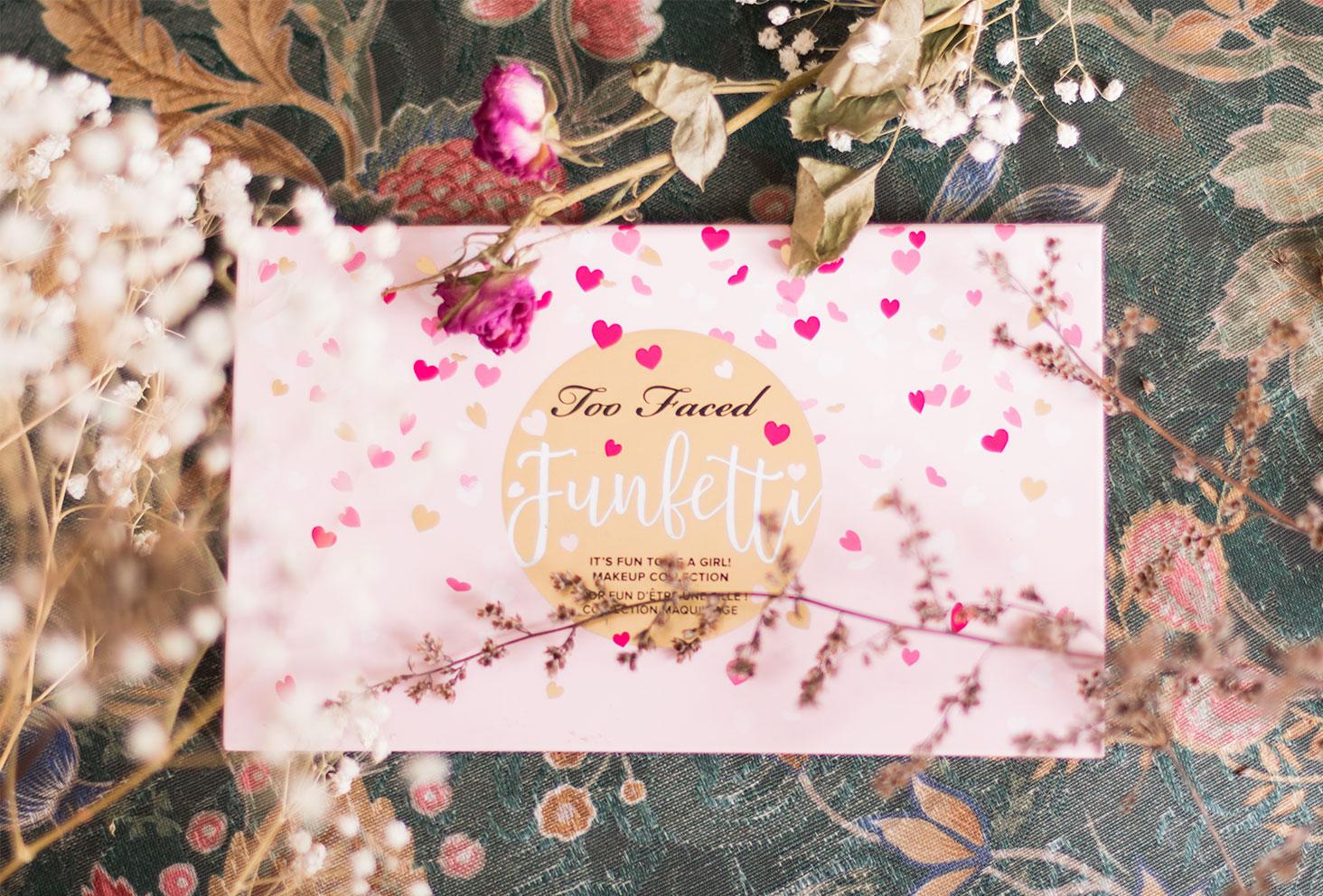 Zoom sur le packaging rose de la palette Funfetti de Too Faced posés entre les fleurs sèches sur un fauteuil fleuri
