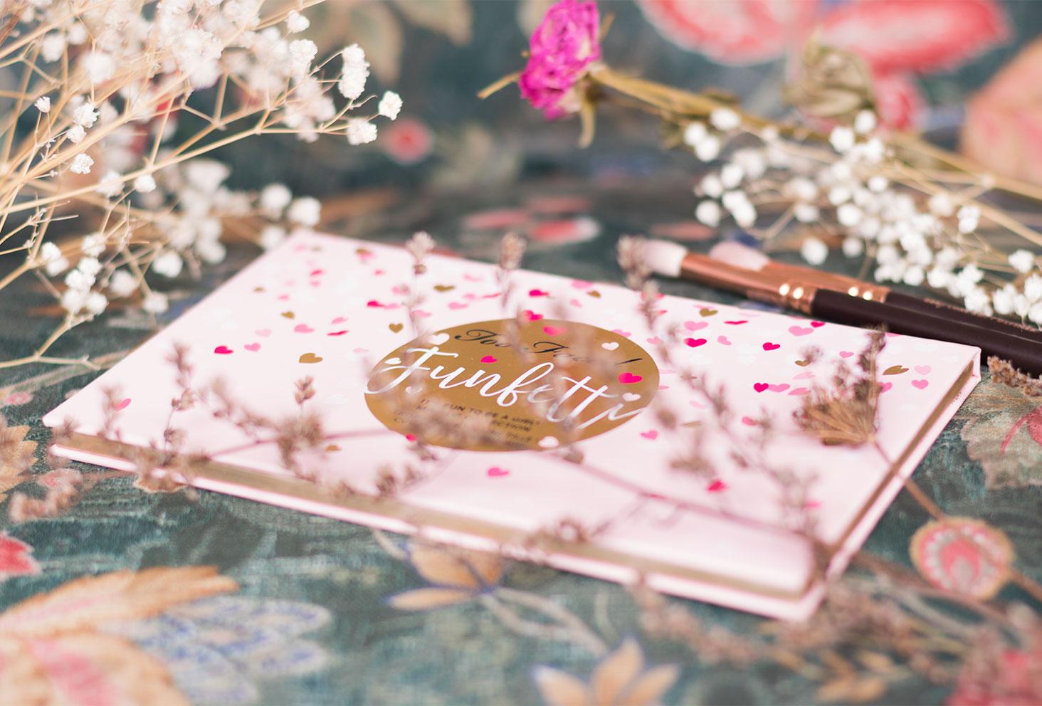 la palette Funfetti de Too Faced avec des pinceaux Zoeva cachés derrière les fleurs séchées