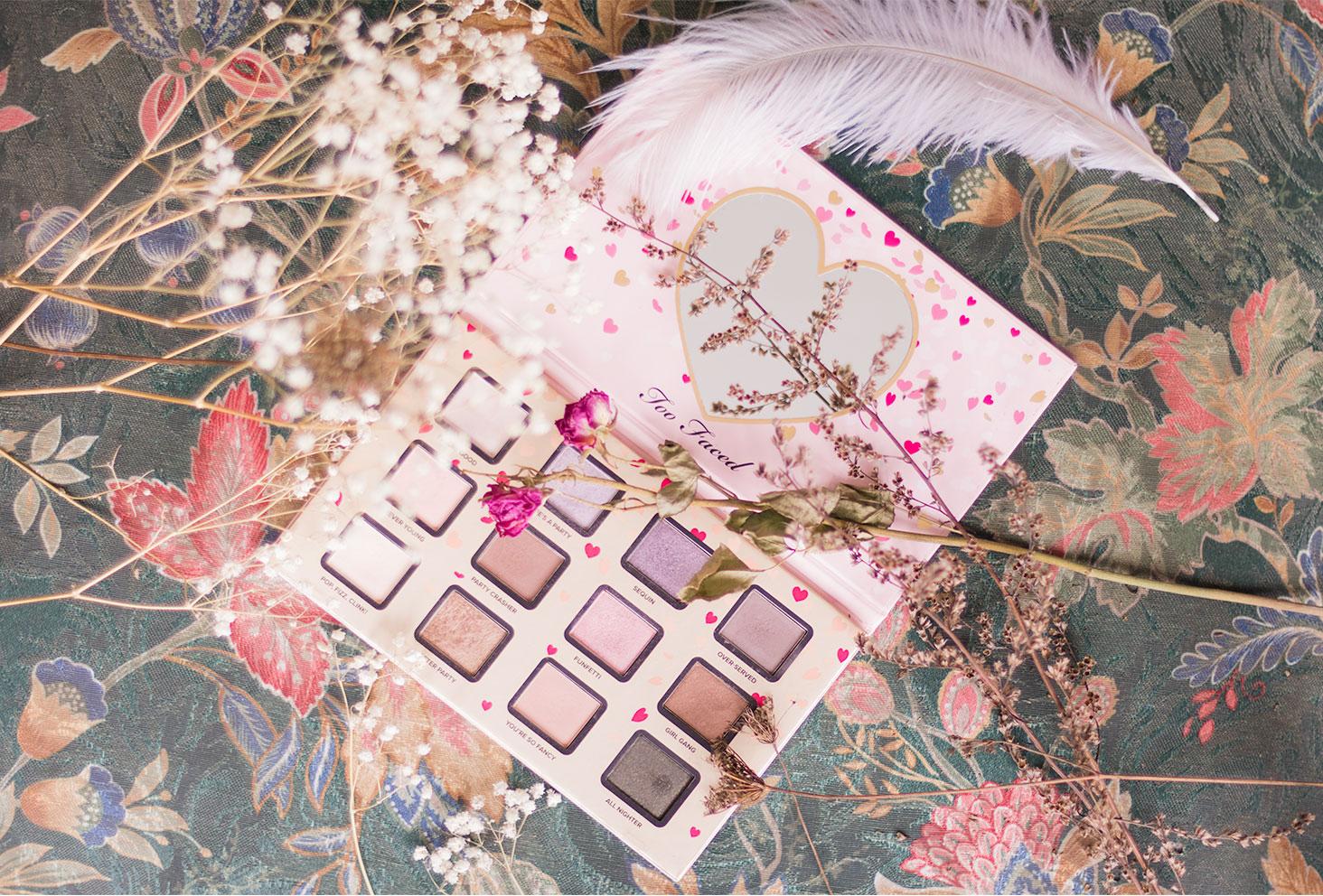 La palette Funfetti de Too Faced ouverte, posé sur un fauteuil fleuri entouré de fleurs séchées
