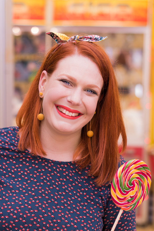 Noeud La Morue dans les cheveux, blouse bleu canard, cheveux roux et sucette géante dans les mains à la fête foraine