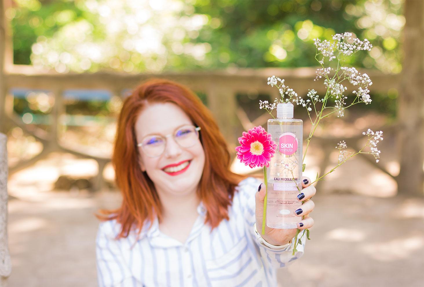 Présentation dans la main de l'eau micellaire de Body Minute tenue entre des fleurs roses et blanches