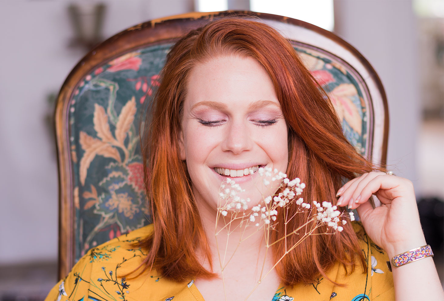 Résultat du make-up réalisé avec la palette Funfetti de Too Faced sur des yeux bleus avec des cheveux roux en robe jaune moutarde à fleurs