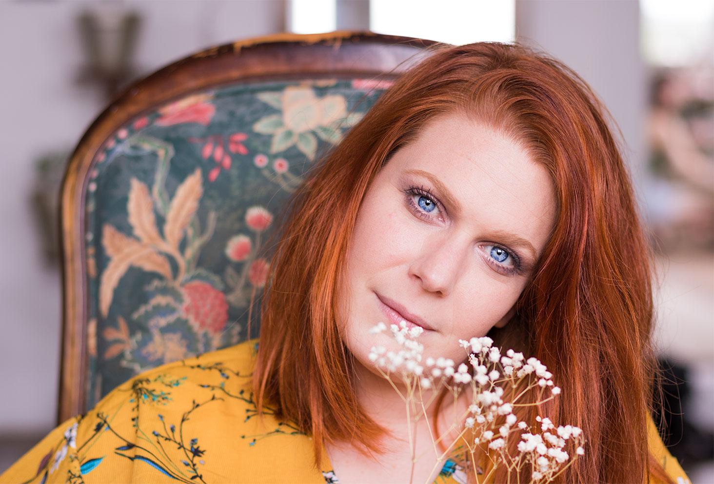 Make-up réalisé avec la palette Funfetti de Too Faced sur des yeux bleus avec des cheveux roux en robe jaune moutarde à fleurs