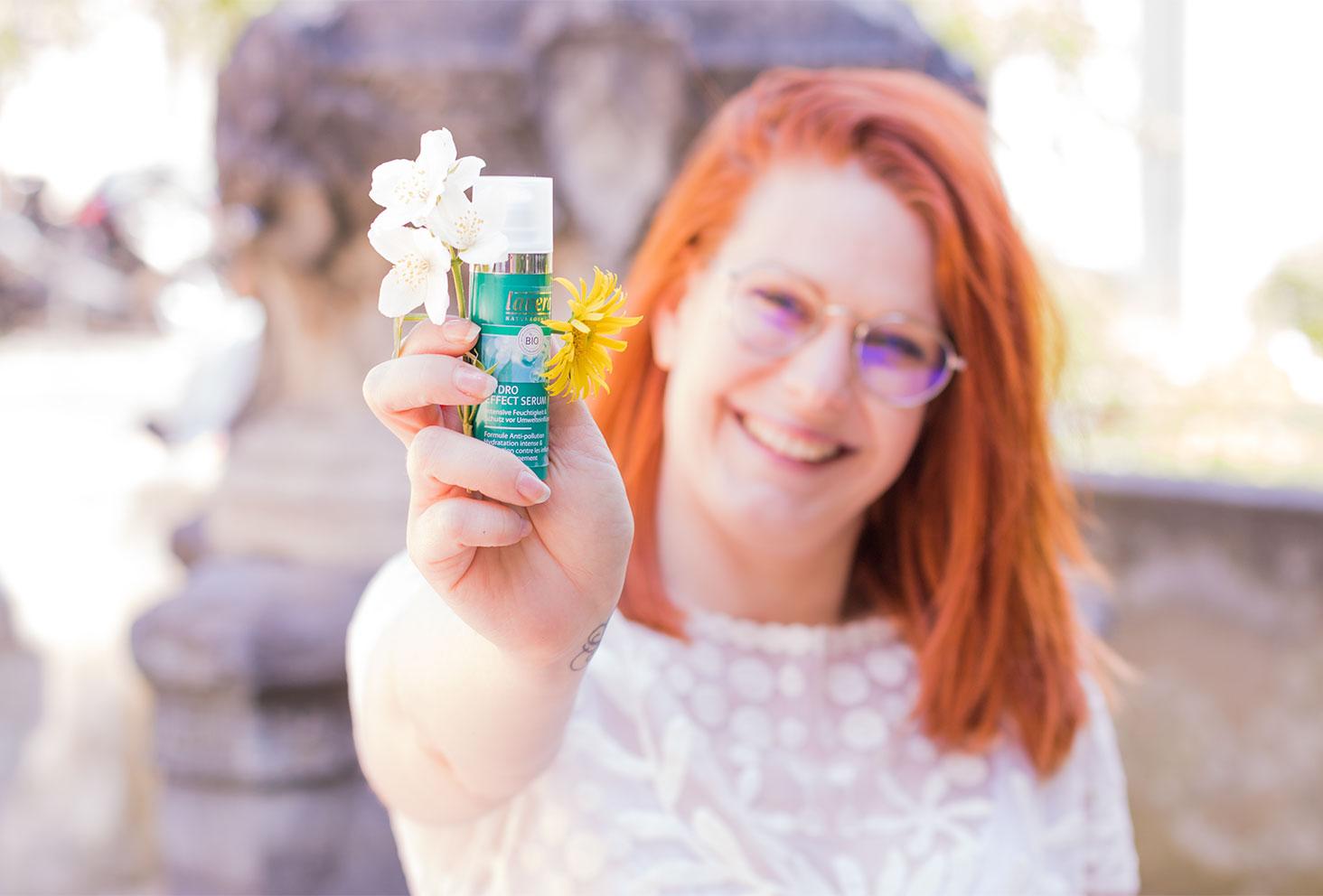 Présentation dans la main avec le visage en arrière plan du sérum anti-pollution de Lavera Naturkosmetik entre les fleurs