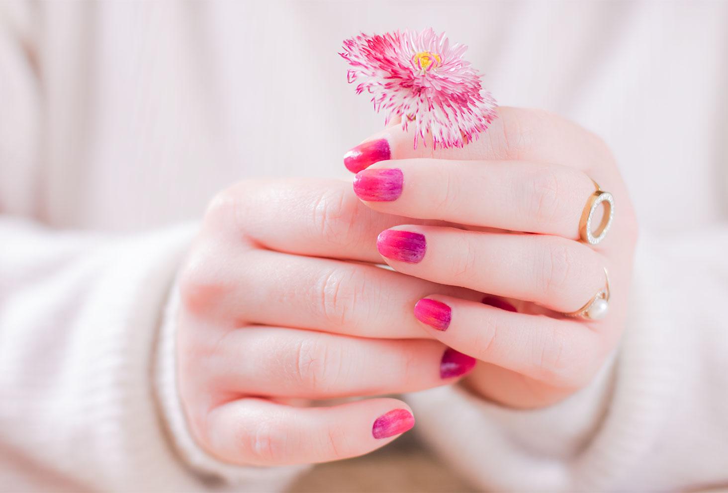 Le nailart dégradé SO'BiO étic sec sur les deux mains tenant une fleur de la même couleur