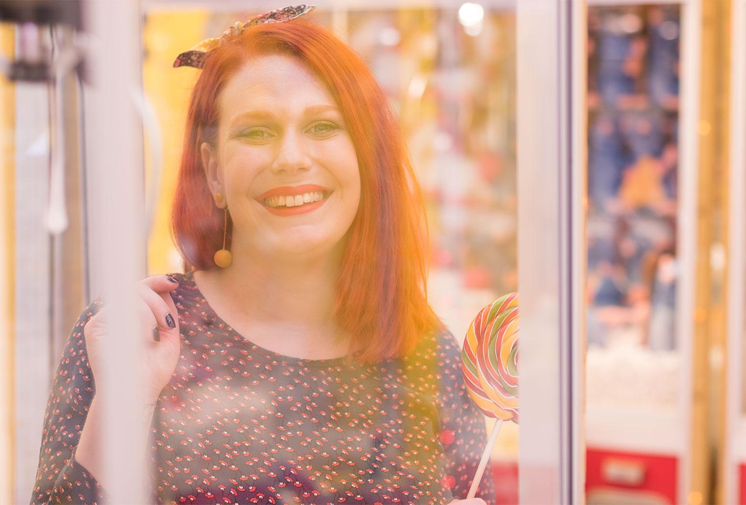 Portrait au travers d'une vitre avec le sourire du rouge à lèvres rouge et boucles d'oreilles jaune