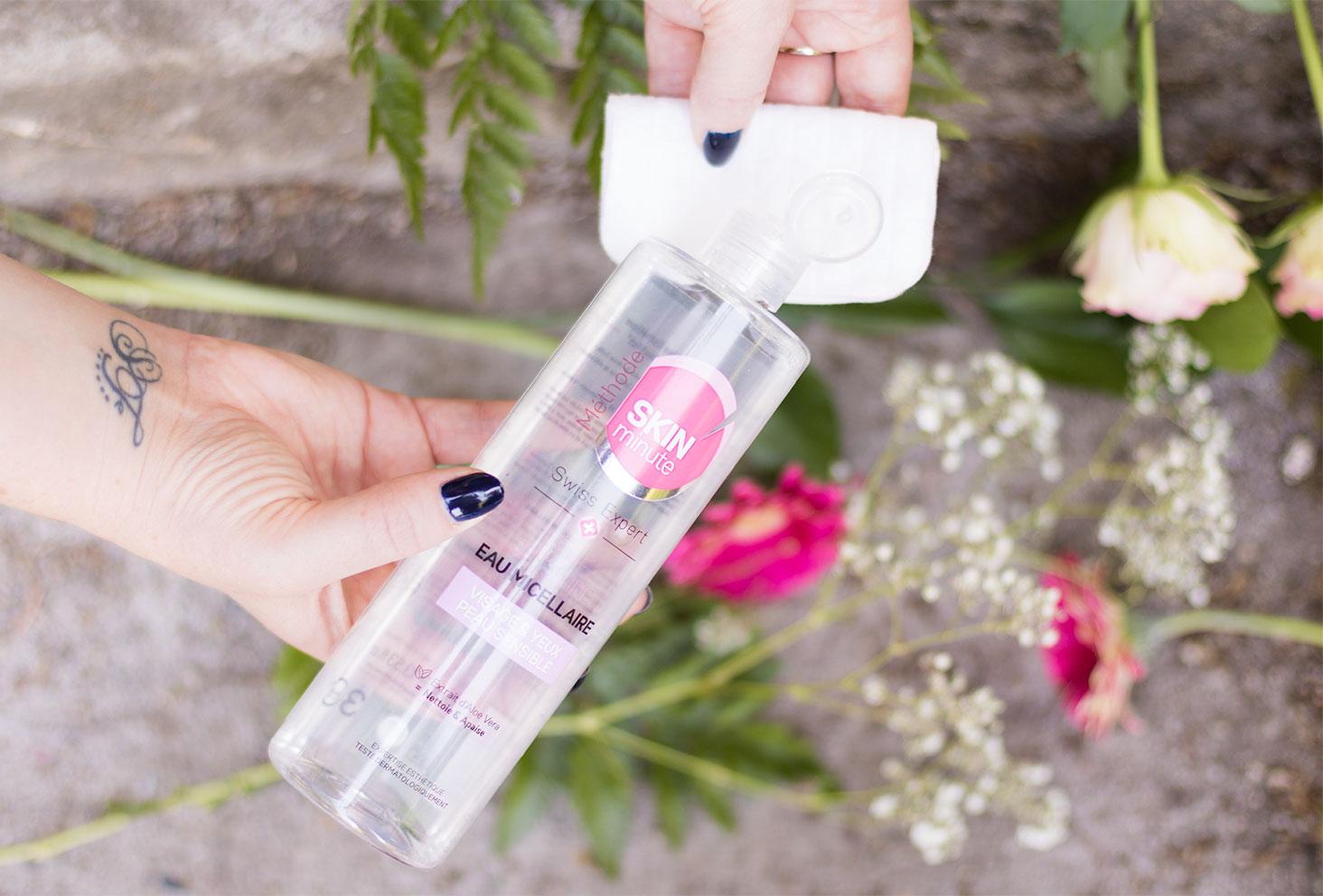 Main qui verse l'eau micellaire de Body Minute sur un coton au dessus des fleurs roses et blanches