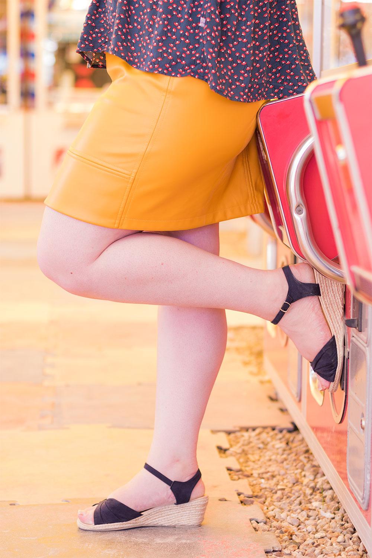 Jupe jaune moutarde et chaussures compensées bleue marine appuyé contre les machines à grappins