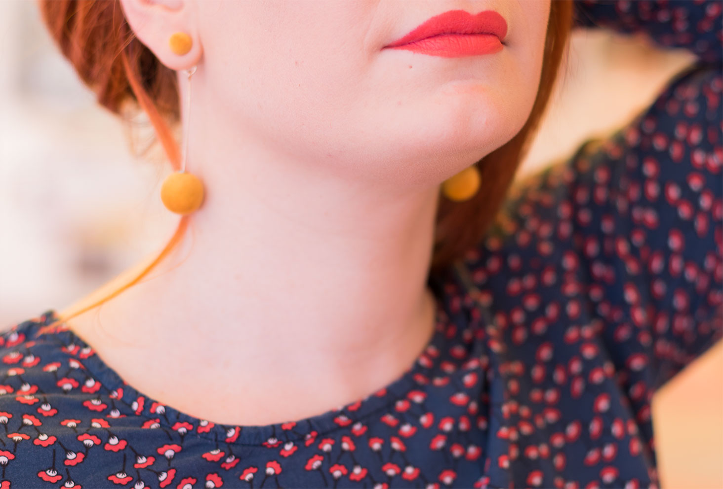 Zoom sur le rouge à lèvre orangé, cheveux remontés par la main et boucles d'oreille jaune moutarde