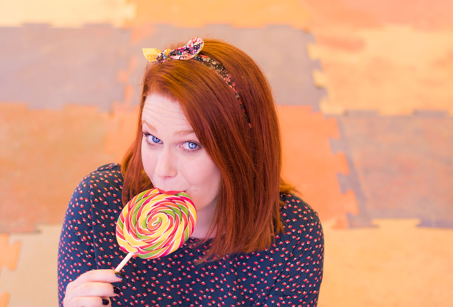 Sucette multicolores dans la bouche à la fête foraine