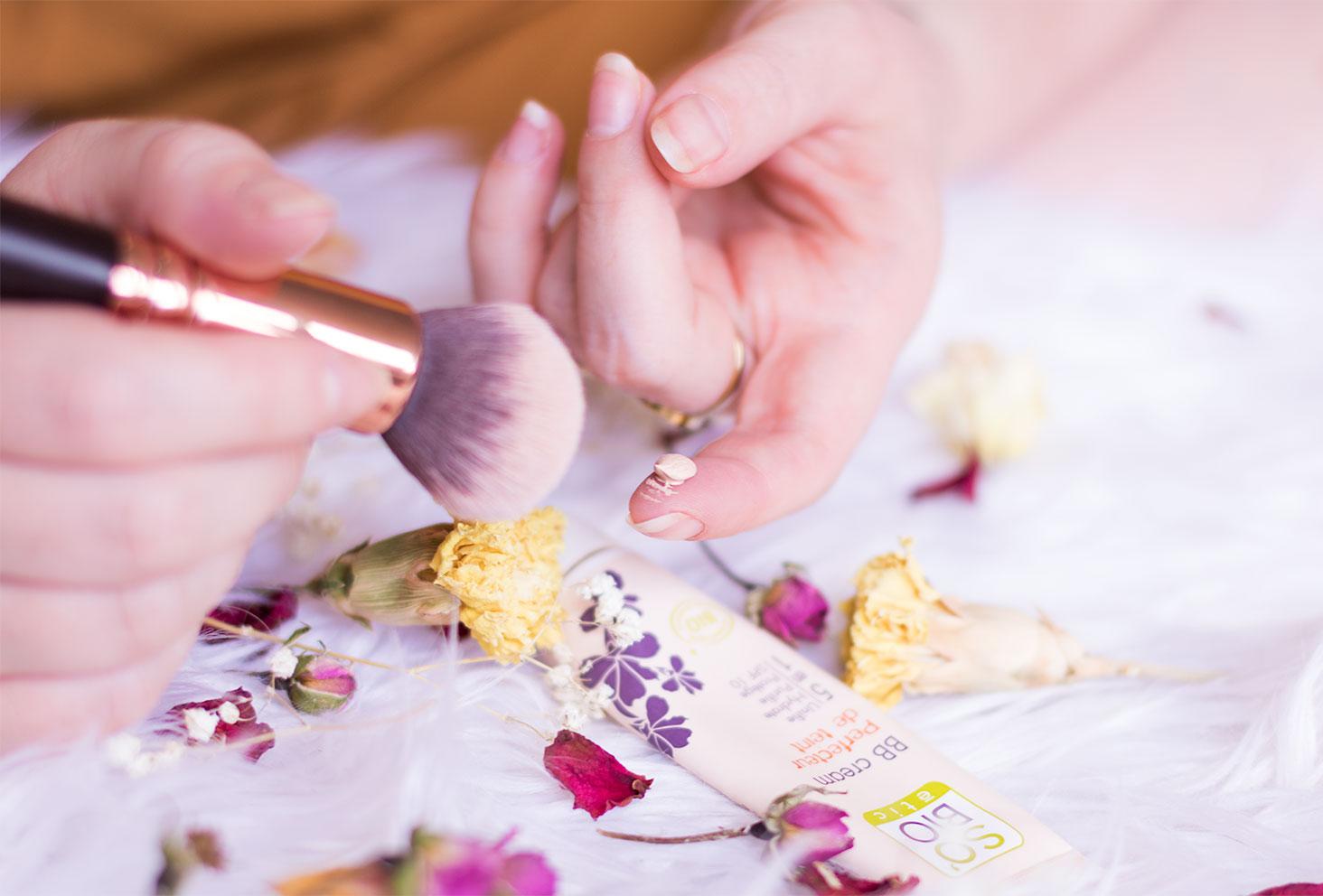 Zoom sur la texture de la BB crème de SO'BiO étic sur le bout du doigt avec le pinceau et les fleurs séchées à côté