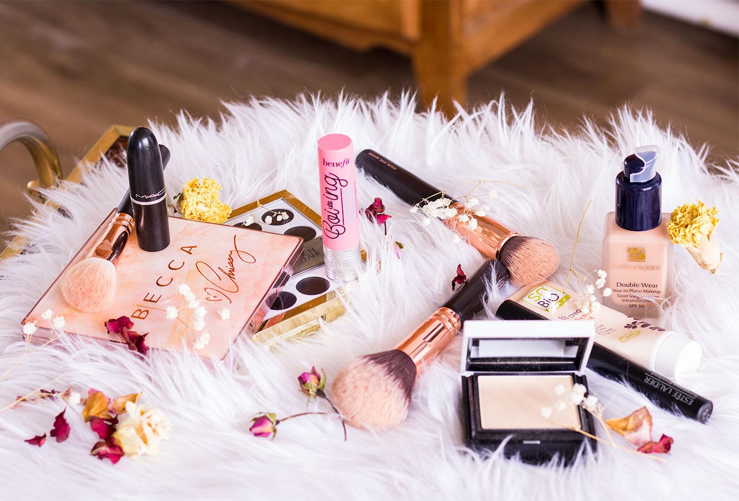 Ensemble du maquillage nécessaire à la réalisation de mon favorite make-up, posé sur un tapis blanc au milieu des fleurs séchées