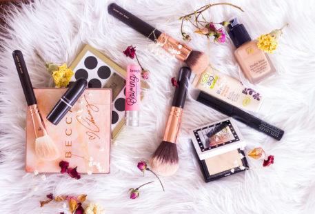 Ensemble de mes produits make-up favoris poszé sur un tapis blanc au milieu des fleurs séchées