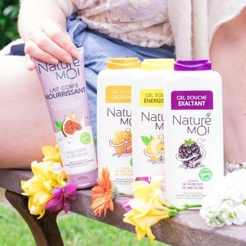 Les gels douche et le lait corps nourrissant de Naturé Moi sur un banc entre les fleurs