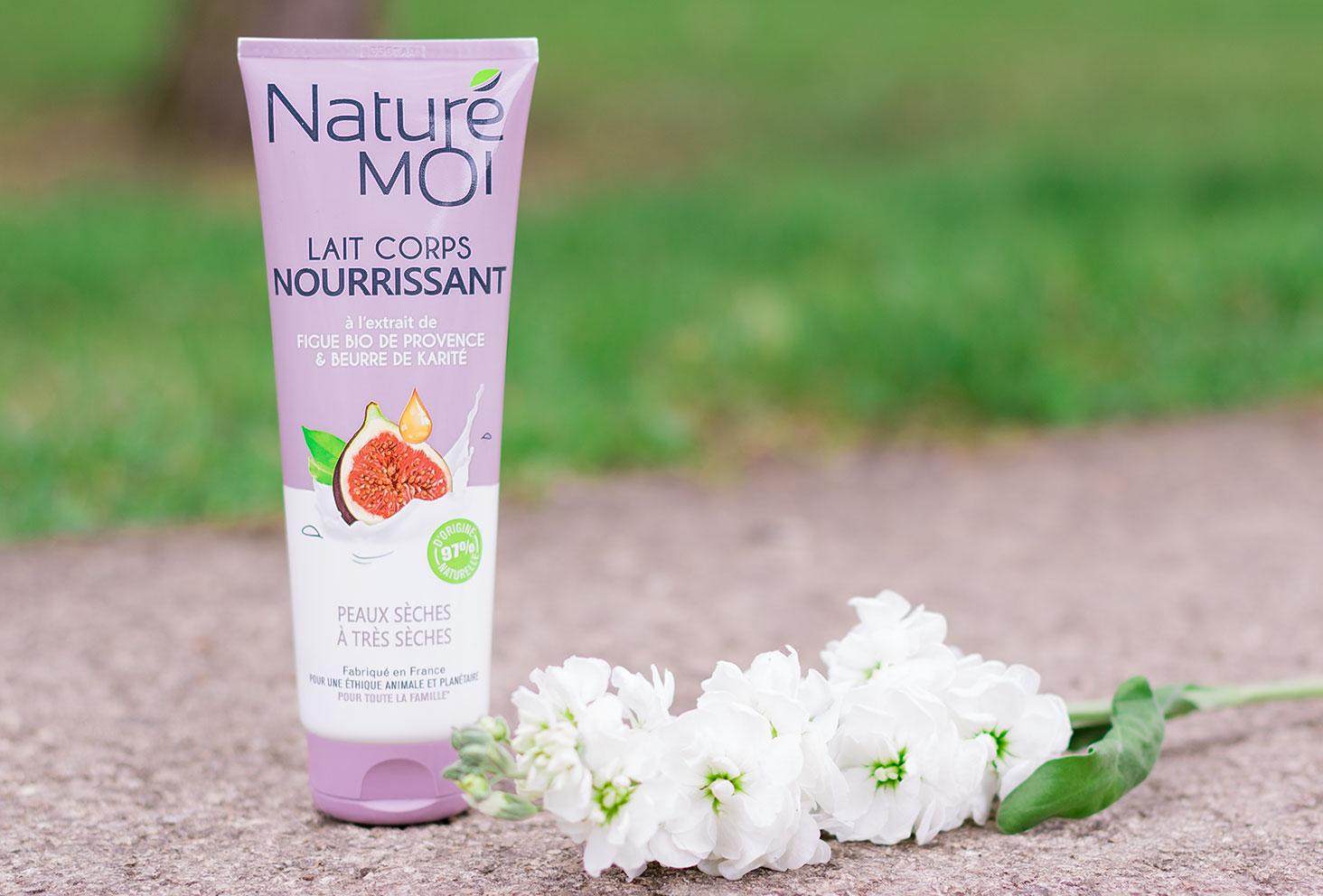 Le lait pour le corps nourrissant Naturé Moi à la figue bio posé sur le sol au milieu des fleurs blanches