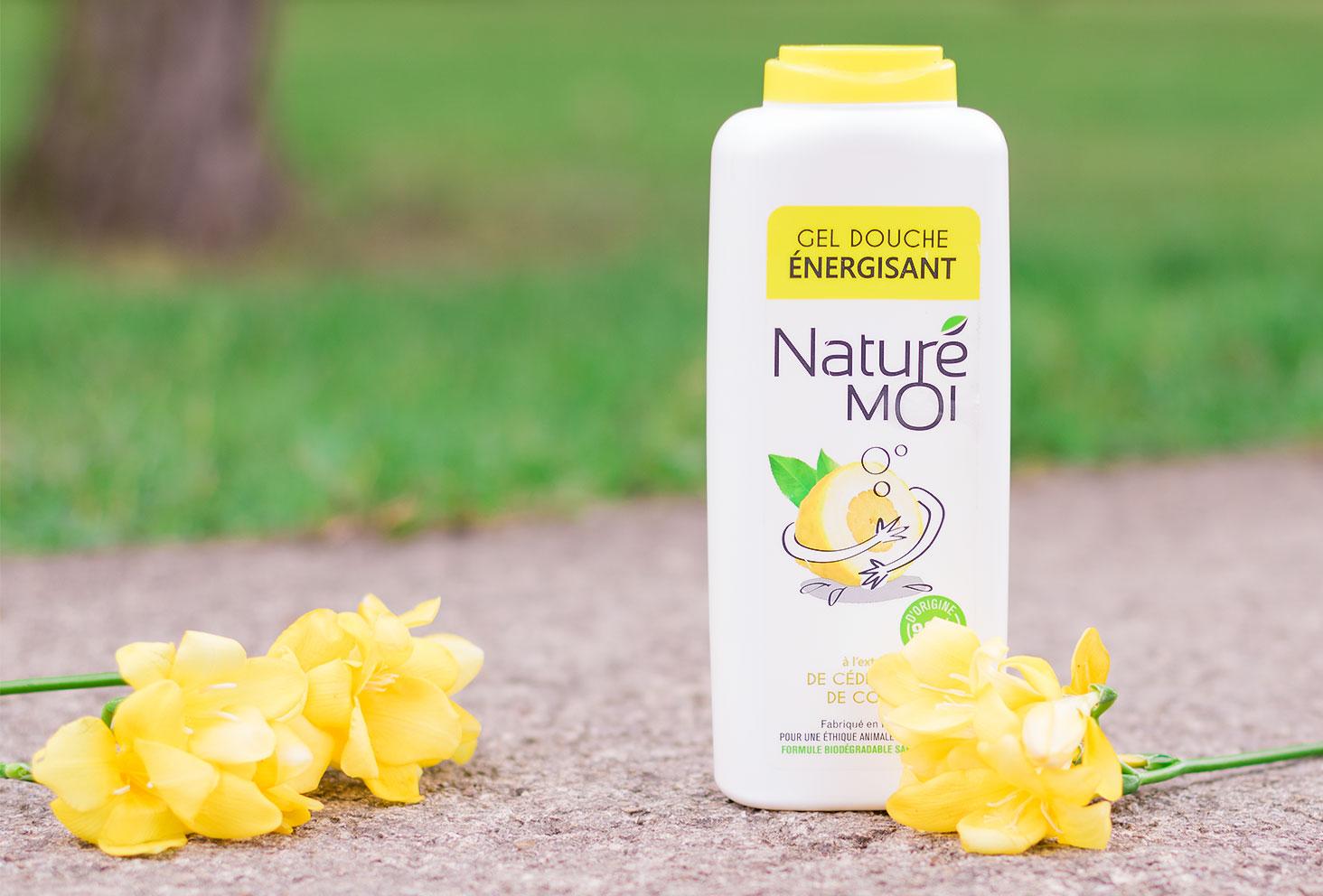 Le gel douche au citron bio Naturé Moi posé sur le sol au milieu des fleurs jaunes