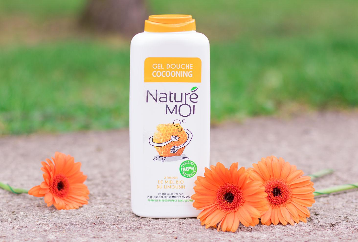 Le gel douche au miel bio du limousin Naturé Moi posé sur le sol au milieu des fleurs oranges