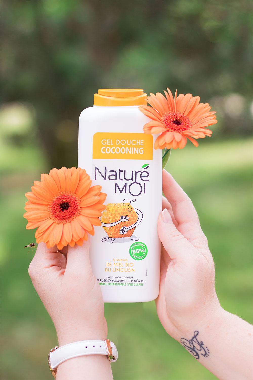 Zoom sur le gel douche au miel bio du Limousin Naturé moi dans la main entre les fleurs oranges