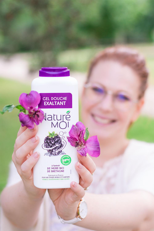 Zoom sur le gel douche à la mûre bio de Bretagne Naturé moi dans la main entre les fleurs violettes