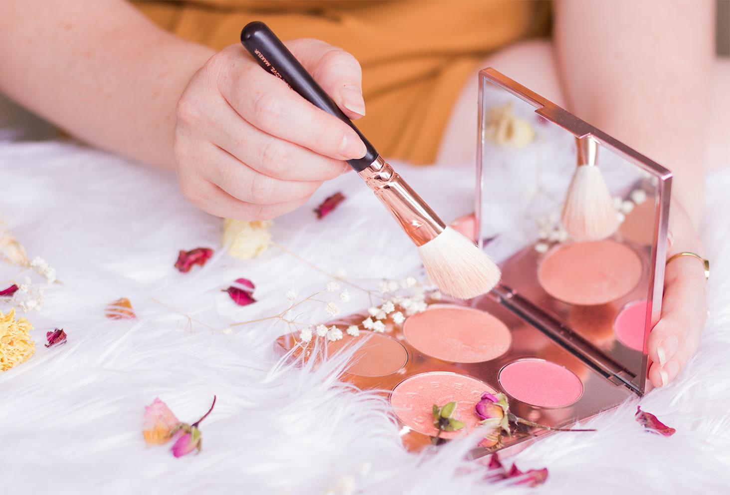 La palette Becca en pleine utilisation de l'highlighter avec un pinceau Zoeva au milieu des fleurs séchées