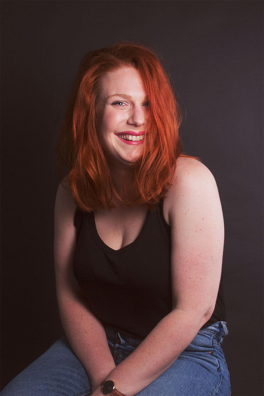 Photo studio sur fond noir assise les bras croisés entre les genoux