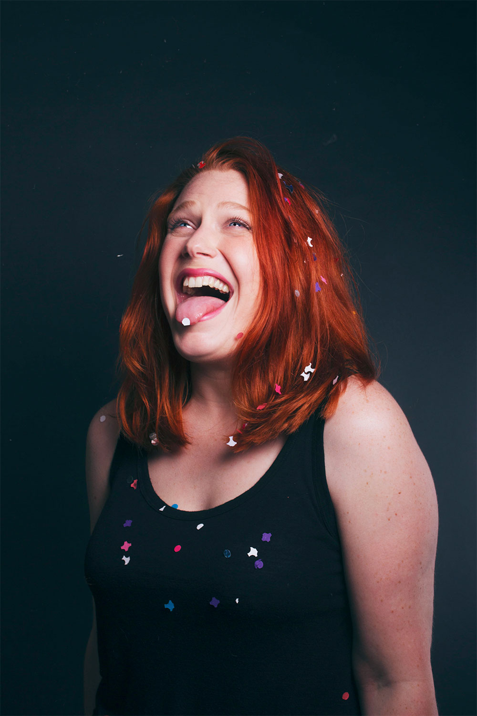 Photo studio sur fond noir avec un confetti sur le bout de la langue