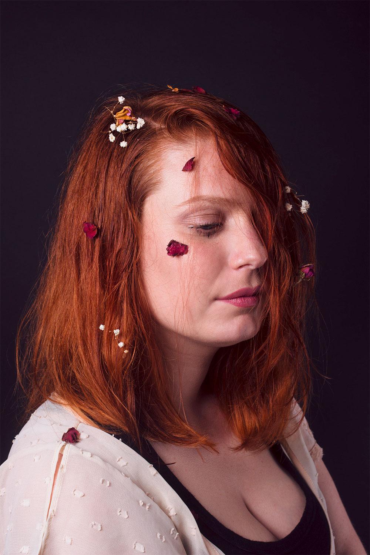 Photo portrait en studio noir avec des fleurs dans les cheveux