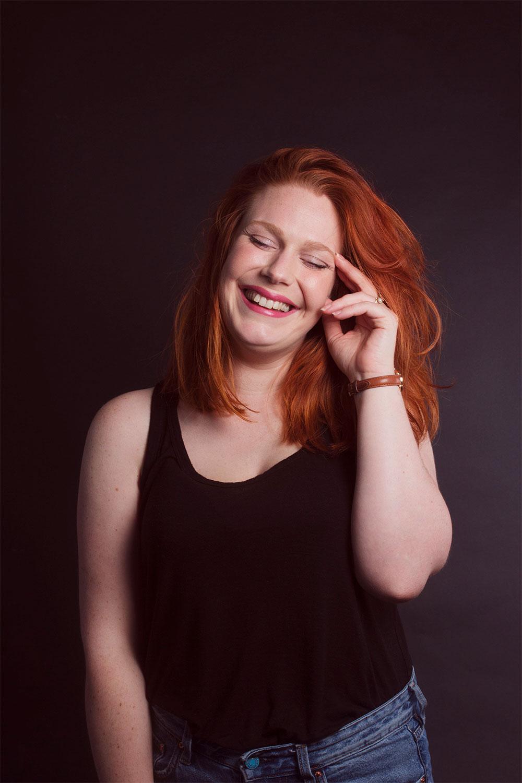 Photo studio debout sur fond noir avec le sourire et la main sur la tempe