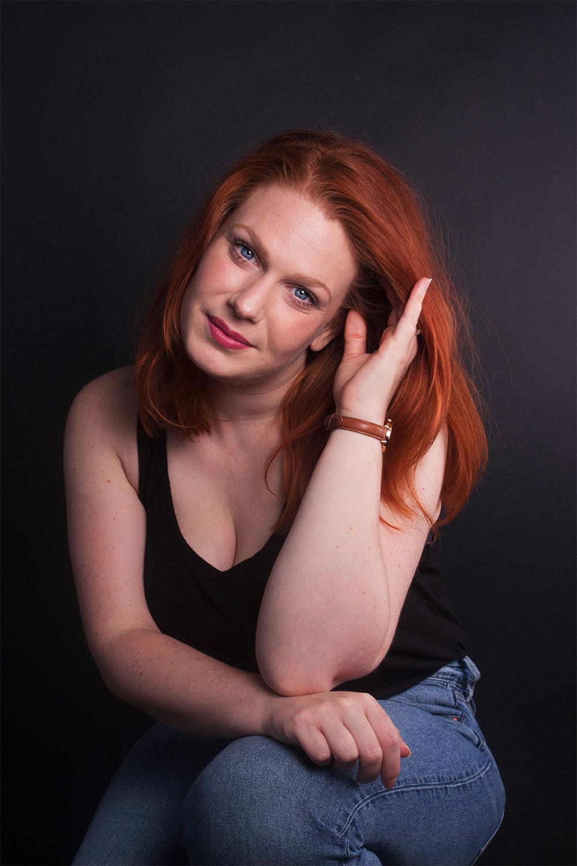 Photo studio avec fond noir, regard bleu et main dans les cheveux