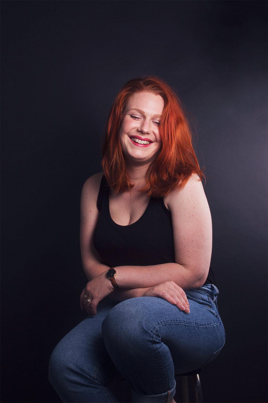 Photo studio fond noir assise avec le sourire et les bras croisés sur les genoux