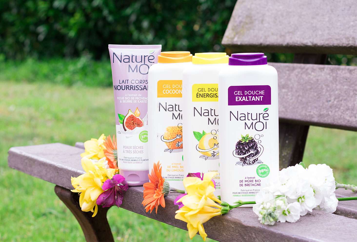Produits Naturé Moi posés sur un banc au milieu des fleurs