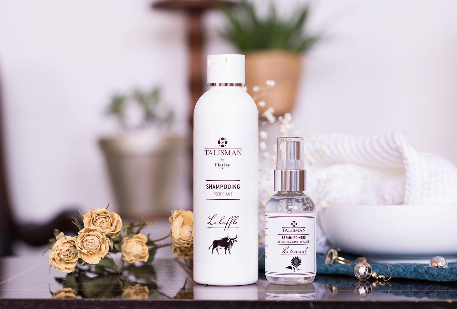 Zoom sur le shampooing fortifiant et le sérum pointes sèches de Talisman sur une table en bois au milieu des fleurs séchées