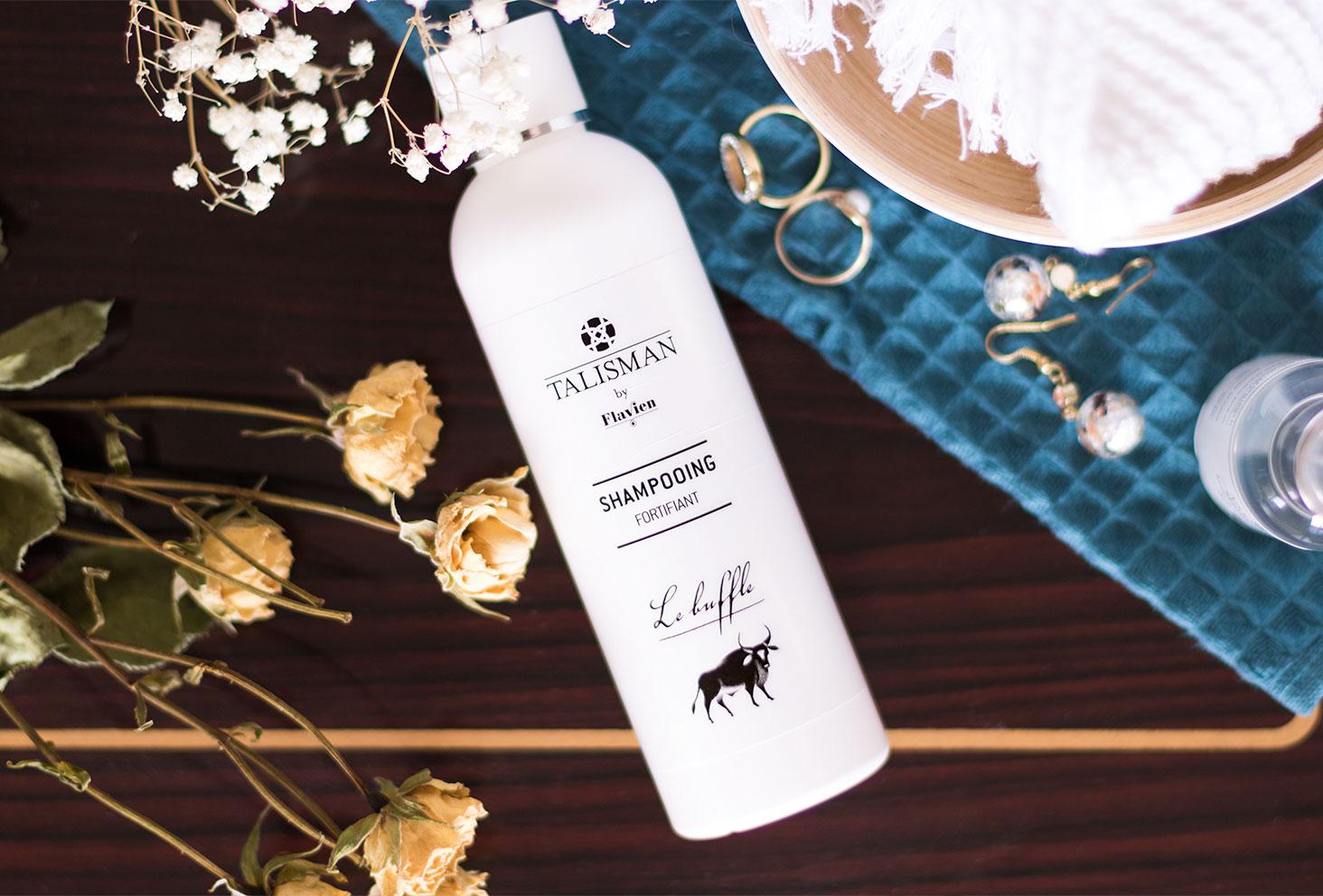 Le shampooing fortifiant de Talisman posé sur une table en bous au milieu des fleurs séchées et des bijoux