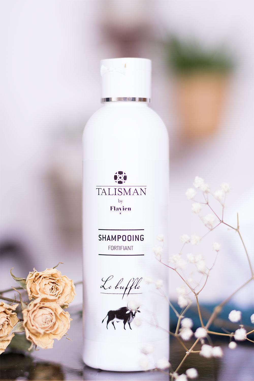 Zoom sur le packaging blanc et noir du shampooing fortifiant de Talisman au milieu des fleurs séchées