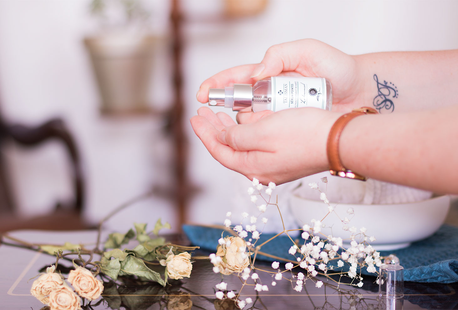 Utilisation de la pompe du sérum pointes sèches de Talisman avec application du produit dans les mains au milieu des fleurs séchées