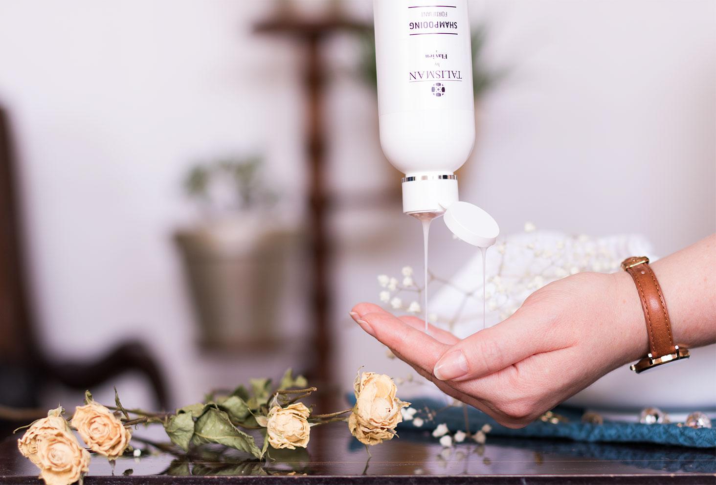 Shampooing fortifiant Talisman la tête en bas avec le produit qui coule dans la main au milieu des fleurs séchées