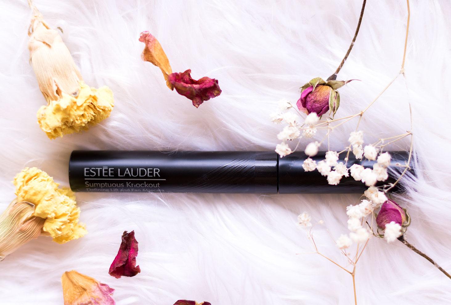 Zoom sur le mascara Somptuous Knockout de Estée Lauder sur un tapis blanc au milieu des fleurs séchées