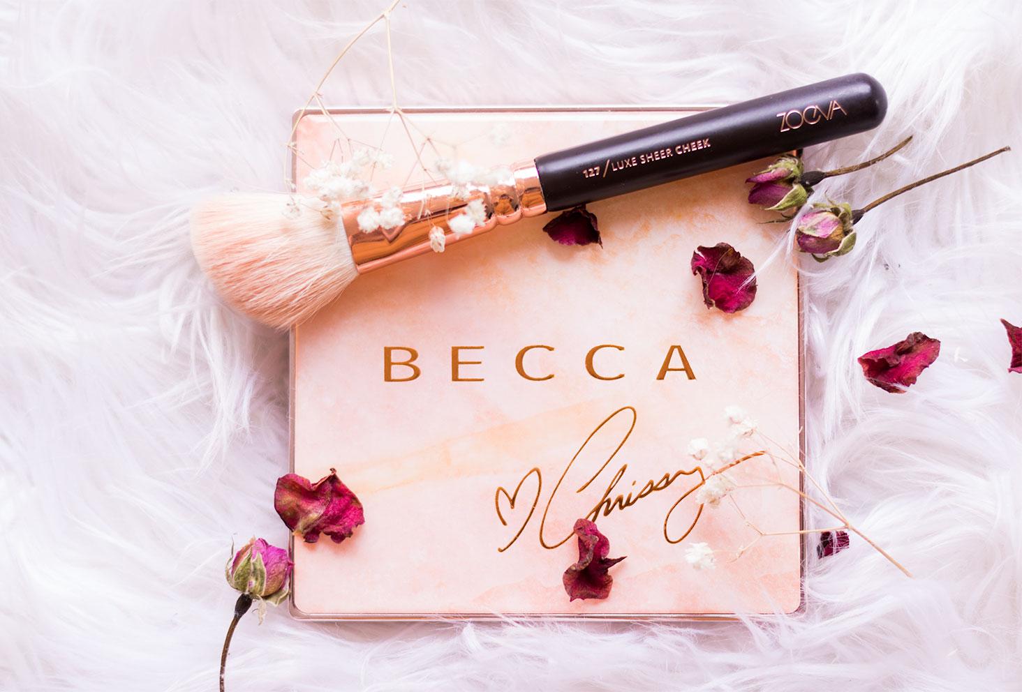 Zoom sur la palette Chrissy de Becca sur un tapis blanc au milieu des fleurs séchées surplombée d'un pinceau ZOEVA