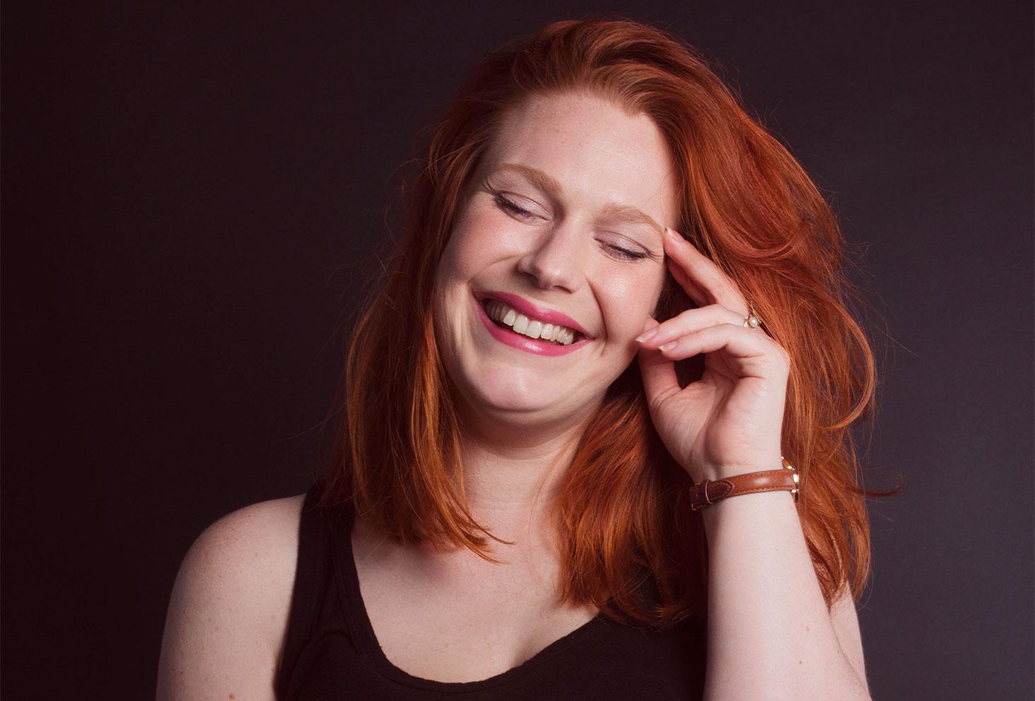 Zoom sur le portrait d'une photo studio fond noir avec le sourire et la main sur la tempe