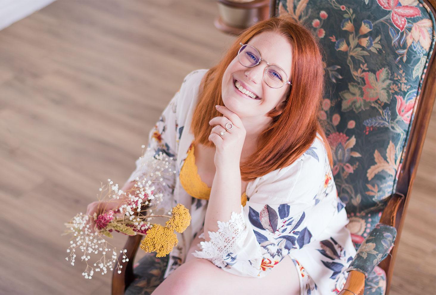 Assise sur un fauteuil vintage, en sous-vêtements et kimono, un bouquet de fleurs dans les mains et le sourire aux lèvres