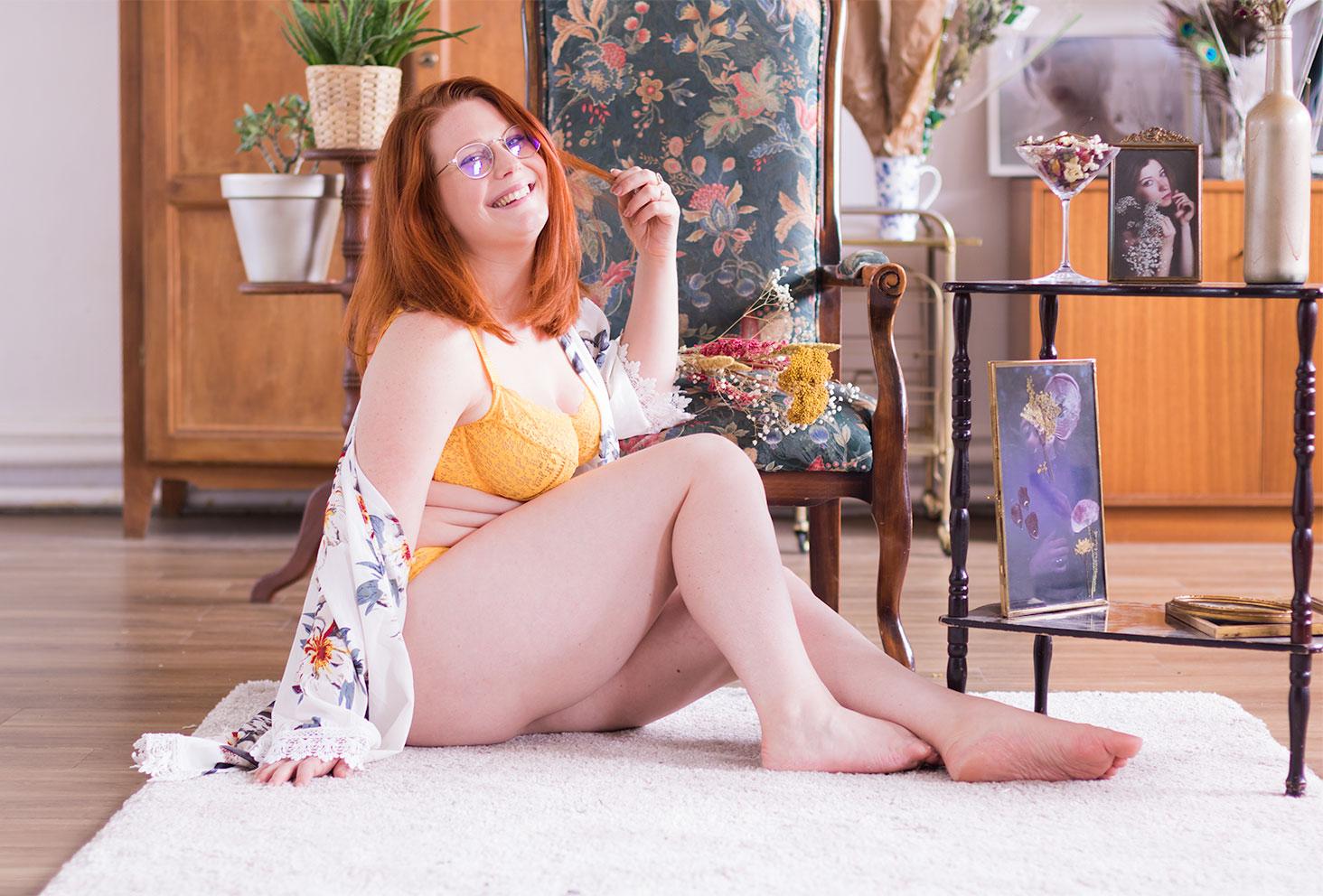 Assise de profil sur un tapis beige au milieu du salon, en sous-vêtements Pomm'Poire et Kimono à fleurs, une main dans les cheveux