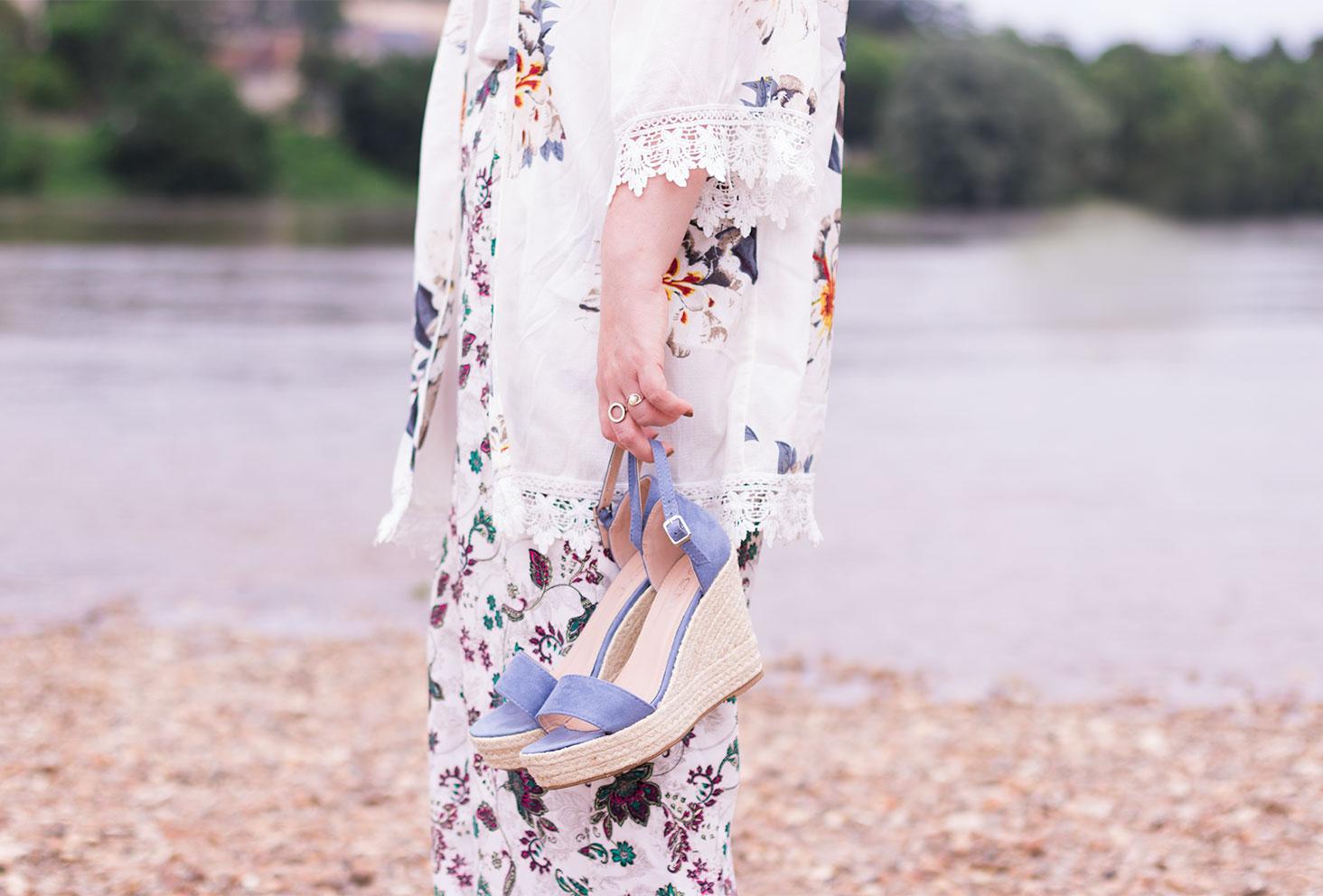 Kimono et pantalon à fleurs, compensées bleues Cendriyon dans la main, avec la Loire en arrière plan