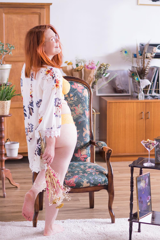 De dos, au milieu d'un salon, en kimono et sous-vêtements en dentelle avec un bouquet de fleurs dans les mains