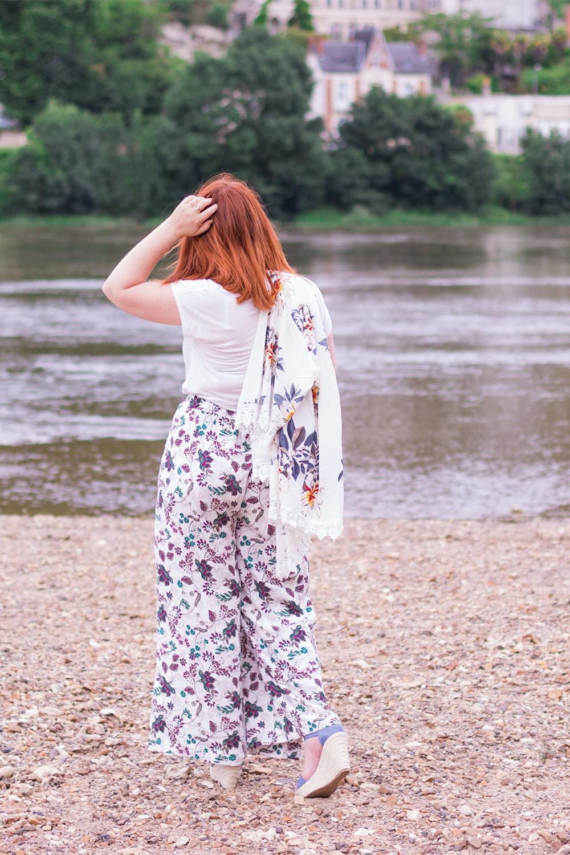 De dos sur la plage des bords de Loire en pantalon à fleurs le Kimono sur l'épaule et les chaussures compensées Cendriyon aux pieds