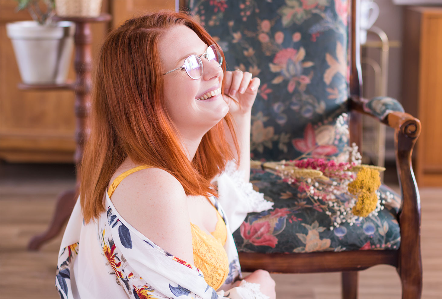 Photo portrait de profil, avec un grand sourire accoudée à un fauteuil fleuri, en sous-vêtements en dentelle jaune Pomm'Poire