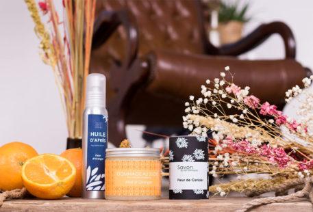 L'ensemble des produits de L'art du Bain au milieu des oranges et des fleurs sèches, sur une planche en bois devant un fauteuil vintage en vieux cuir marron