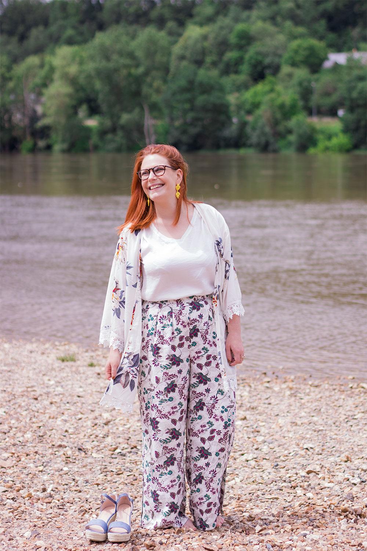 Kimono a fleurs, pantalon fleurit et compensées posées sur le sable d'une plage sur les bord de Loire
