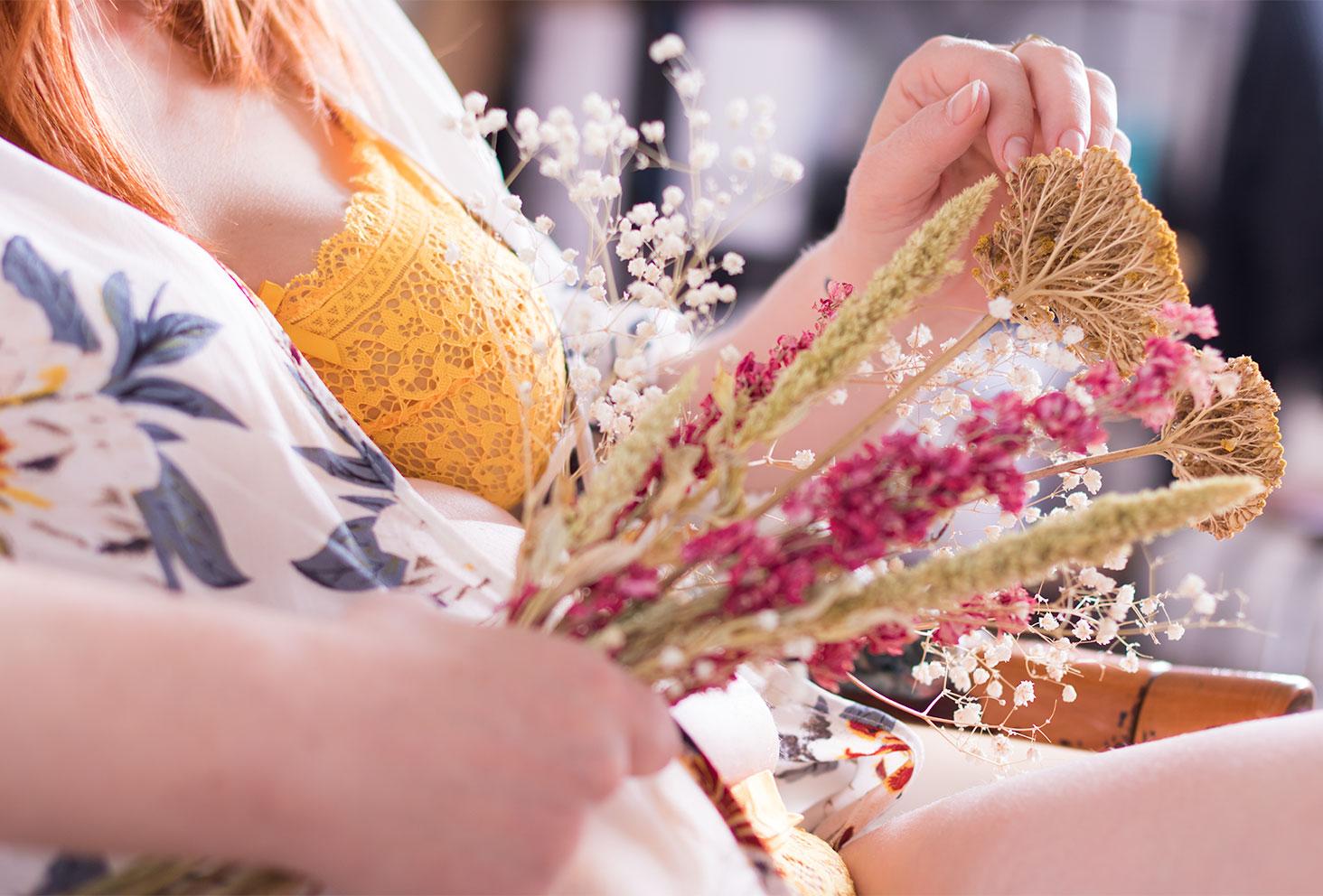 Bouquet de fleurs séchées dans les mains sur le ventre, devant les sous-vêtements en dentelle jaune Pomm'Poire portés