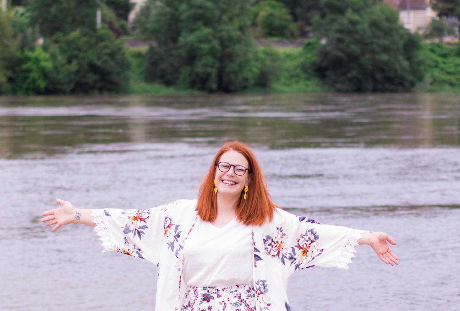 Les bras écarté avec la Loire derrière, en kimono blanc à fleurs et boucles d'oreilles jaunes